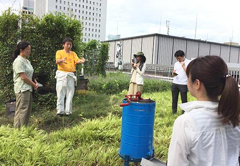 ビルの屋上での養蜂活動を指導する田中さん